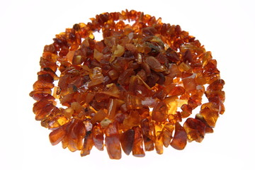 Stones of amber and a necklace on white background