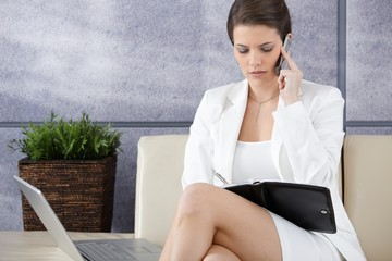 Businesswoman waiting in office lobby, working