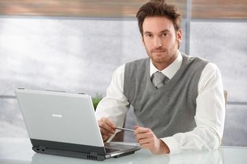 Handsome businessman working on laptop