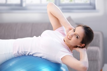 Attractive girl exercising on fit ball smiling