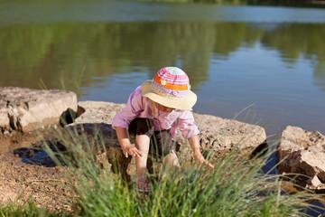 mädchen mit sonnenhut spielt am see