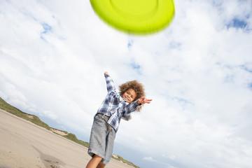 Boy playing frisbee on beach