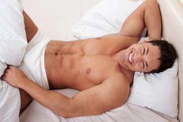 Happy man lying in his bed
