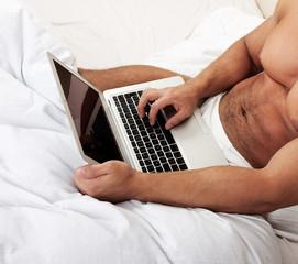 Man using laptop, sitting on bed