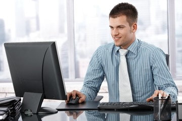 Young businessman working in modern office smiling