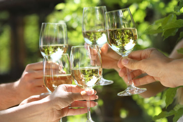 People holding glasses of white wine making a toast
