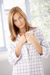 Young female drinking morning coffee in pyjama
