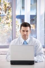 Portrait of confident businessman with laptop