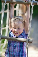 lachendes kind hängt an einer strickleiter
