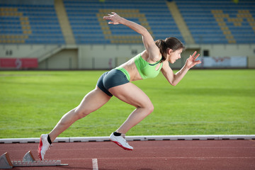 Action packed image of a female sprinter leaving starting blocks