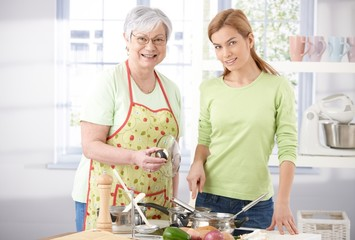 Pretty girl cooking with senior mother smiling