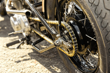 Wall Mural - motorcycle wheel and drive-chain with golden toned highlights