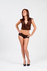 Jolie jeune femme mince posant sur fond blanc en boxer marron