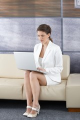 Businesswoman in office lobby with laptop
