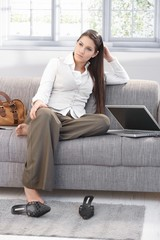 Weary businesswoman sitting on sofa