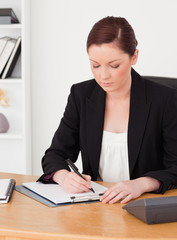 Beautiful red-haired woman in suit writing on a notepad