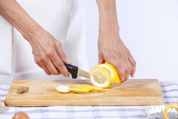 Hands cutting lemon