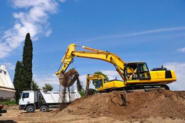 Excavator loading earth on truck