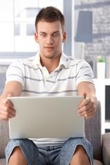 Young man staring at laptop screen horrified