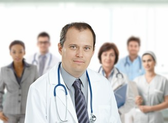 Confident male doctor in front of medical team