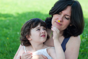 Adorable little girl giving a flower to her mother