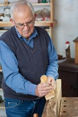 älterer mann hobelt in der werkstatt