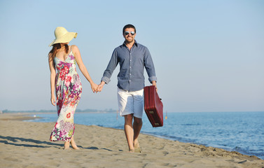 couple on beach with travel bag