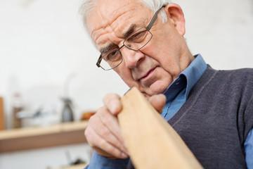 älterer schreiner prüft holz