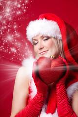 Frau im Weihnachtskostüm mit Herz und Sternschnuppen