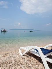 Deck chair on beach with a view at blue sea and island Hvar