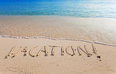 "On a beach it is written ""VACATION"""