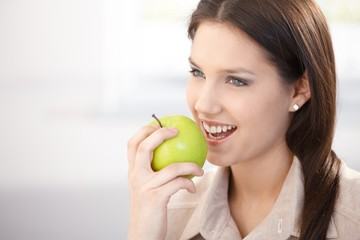 Pretty woman eating green apple smiling