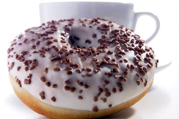Donut mit Schokostückchen garniert vor weißer Tasse