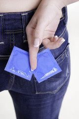 Zwei Kondome hinter einem Rücken