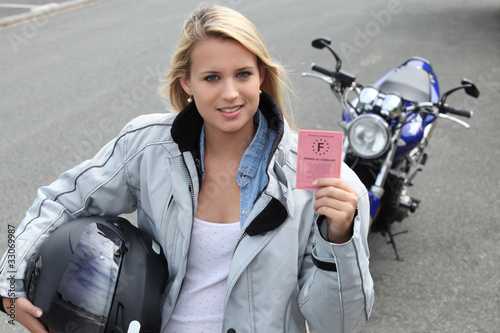 Wall mural Young woman with motorcycle and French license