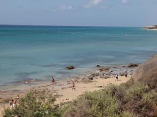 Spaziergänger am Sandstrand mit Blickrichtung auf das Meer