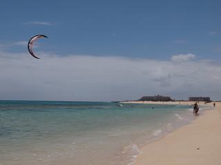 Kitesurfer läuft am Strand entlang und führt seinen Schirm in der Luft mit sich