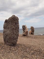 Drei Felssteine in Küstennähe mit Blick auf das Meer im Hintergrund