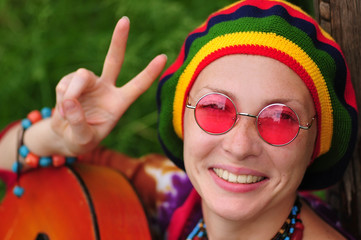 Young hippy woman making peace sign