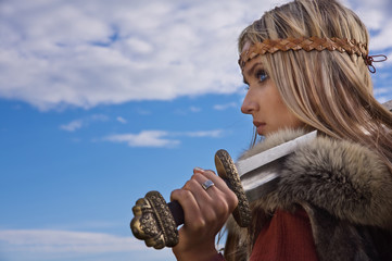 Viking girl warrior on a blue sky background