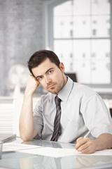 Young man working in office writing notes thinking
