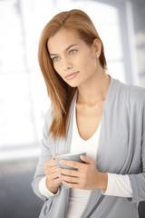 Dreamy young woman with coffee mug
