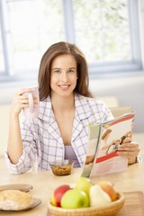 Happy woman at breakfast with magazine
