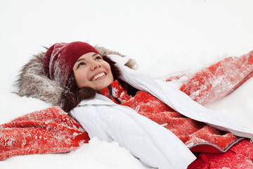 Happy girl lying down on  snow