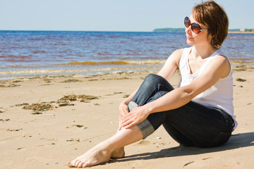 Woman in sunglasses on the beach.