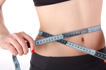Fitness woman measuring her waist