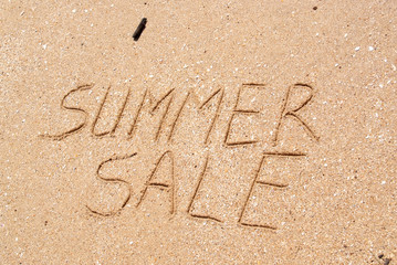 The word Summer Sale written in the sand