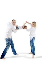 Father and mother in white shirts and jeans swing child