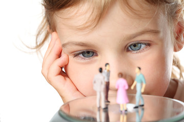 little girl looks at small toy figures of people isolated