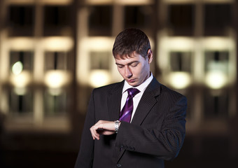 Handsome businessman watching time at night city in the backgrou